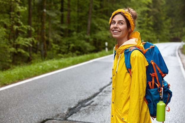 Positieve jonge vrouw met rugzak, staat zijwaarts op camera, loopt over de weg