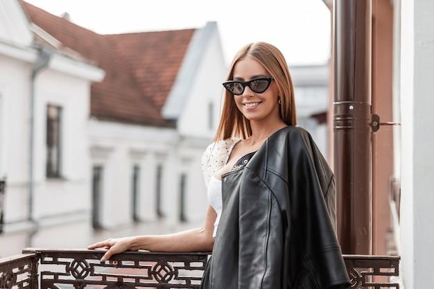Positieve jonge vrouw model in modieuze zonnebril in een stijlvolle zwarte jas poseren op een vintage balkon met uitzicht op witte huizen. mooie hipster meisje met een mooie glimlach is buiten ontspannen.