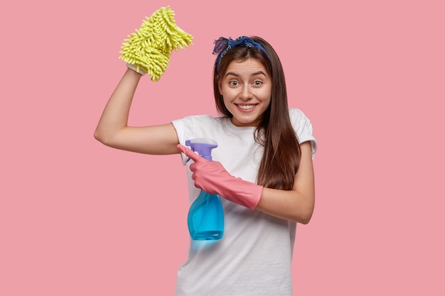 Positieve jonge vrouw toont spieren na moe werk over huis, gekleed in wit casual t-shirt, houdt een fles spray