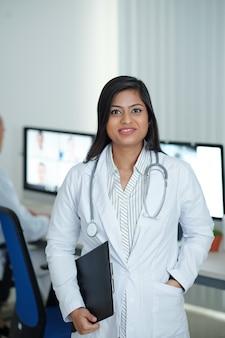 Positieve jonge vrouwelijke arts die in het medische kantoor staat met klembord in de hand, klaar om zieke patiënten te bezoeken