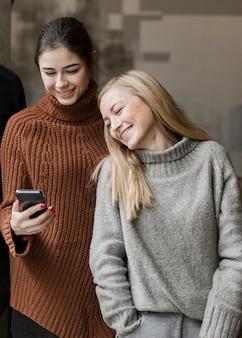 Positieve jonge vrouwen die op een video op een telefoon letten