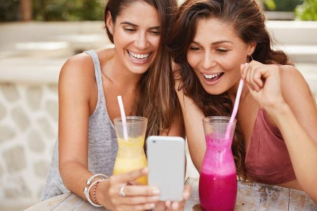 Positieve jonge vrouwtjes met gelukkige vrouwtjes kijken naar grappige video's op de smartphone, drinken cocktails