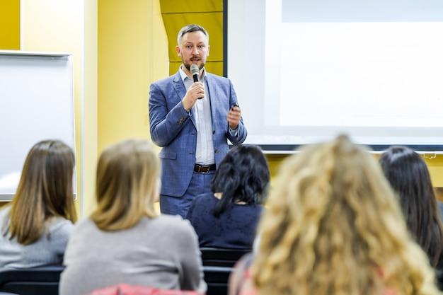 Positieve jonge zakenman die een presentatie doet aan zijn collega's. knappe man met microfoon. jonge professional in de buurt van het bestuur. selectieve aandacht.