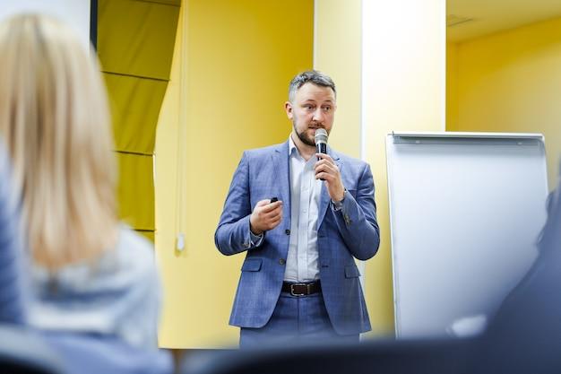 Positieve jonge zakenman die een presentatie doet aan zijn collega's. knappe man met microfoon.