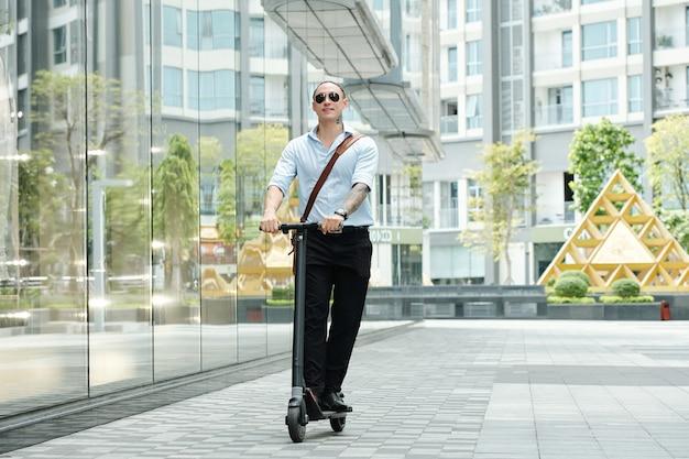 Positieve jonge zakenman die genieten van het rijden op de scooter langs de straat in de stad
