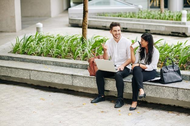 Positieve jonge zakenmensen die koffiepauze buitenshuis doorbrengen en een nieuw project en marketingstrategie bespreken