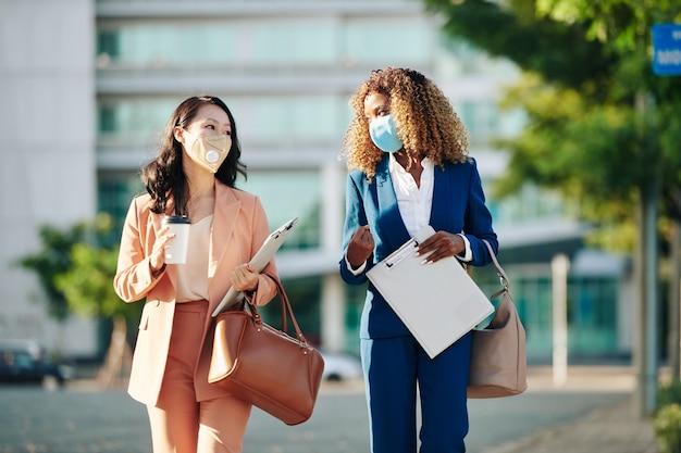 Positieve jonge zakenvrouwen met beschermende maskers die naar huis lopen na op kantoor te hebben gewerkt en een groot project te bespreken