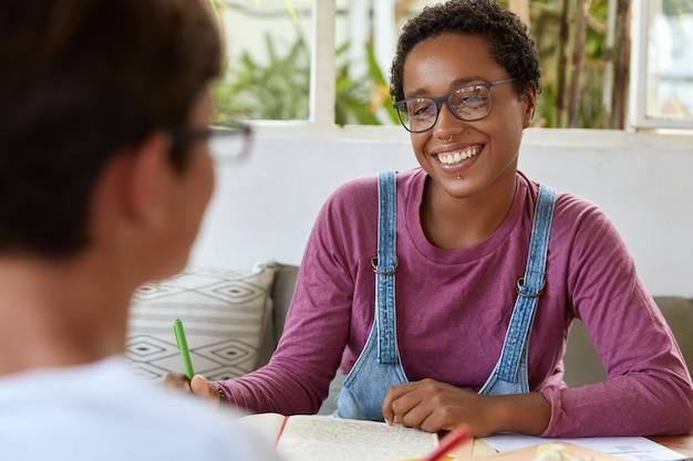 Positieve jonge zwarte vrouwelijke journalist in bril