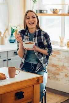 Positieve jongedame die lacht en ontbijtgranen eet uit de kom in haar keuken