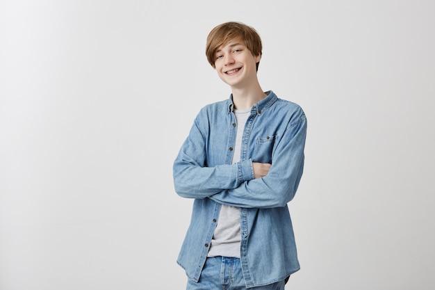 Positieve jongeman in spijkerblouse met blond haar en blauwe ogen, verlegen, nerveus glimlachend in gesloten houding, armen gekruist terwijl hij met een meisje praat, hij houdt van