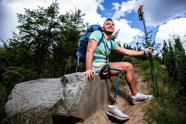 Positieve jongeman met prothese die geniet van nordic walking terwijl hij uitrust