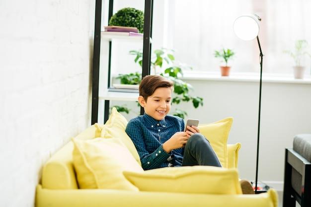 Positieve jongen die thuis ontspant en naar het scherm van zijn moderne apparaat kijkt terwijl hij op gele bank zit