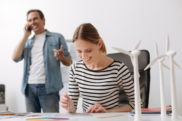 Positieve kantoorsfeer. vrolijke professionele vrouwelijke ingenieur aan de tafel zitten en een tekening maken terwijl haar collega op de achtergrond over slimme telefoon praat