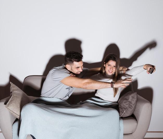 Positieve kerel die hand aan tv verre hand van damehand bereikt op bank
