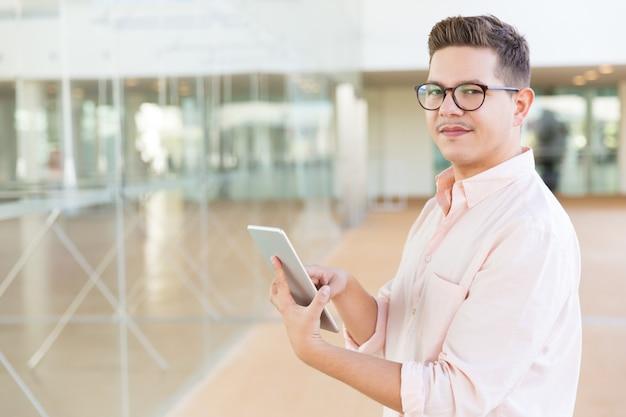 Positieve kerel die in glazen tablet in bureau of hotelzaal houden