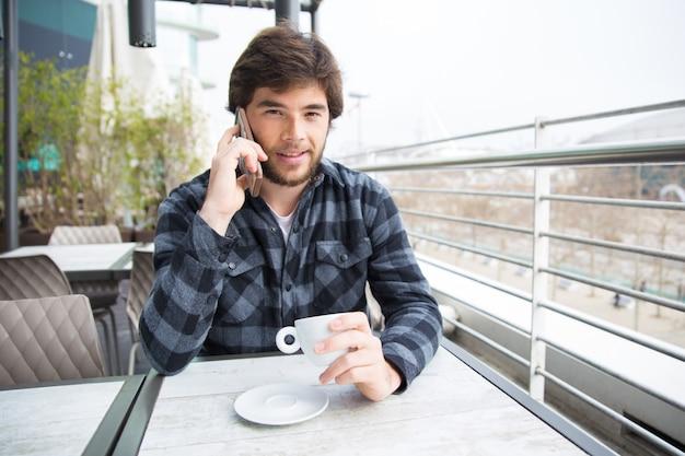 Positieve kerel die van koffie en aardig telefoongesprek geniet