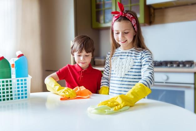Positieve kinderen maken de keukentafel schoon. glimlachende jongen en meisje wrijven het stof in het huis. huishoudconcept