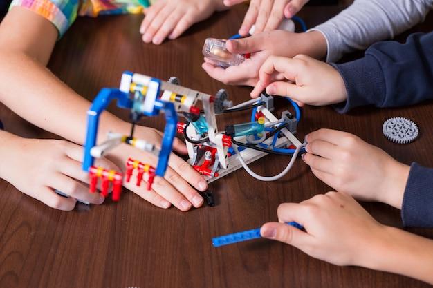 Positieve kinderen spelen en monteren de constructeur in de kinderkamer.