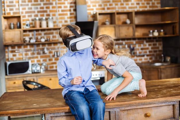 Positieve kleine broers en zussen die plezier hebben tijdens het testen van een vr-apparaat