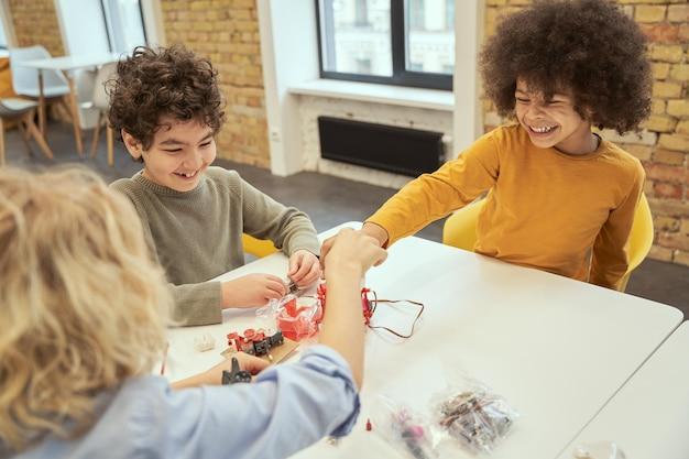Positieve kleine diverse jongens die lachen terwijl ze aan tafel zitten en details van een robot onderzoeken