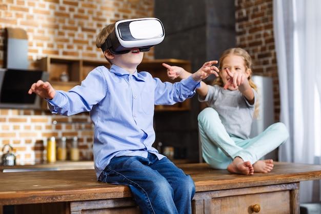 Positieve kleine jongen test vr-apparaat terwijl hij uitrust met zijn zus