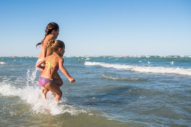 Positieve kleine meisjes rennen langs de stormachtige golven op een zonnige warme zomerdag. het concept van actieve kinderspellen op het strand. zeetocht met kinderen. advertentie ruimte