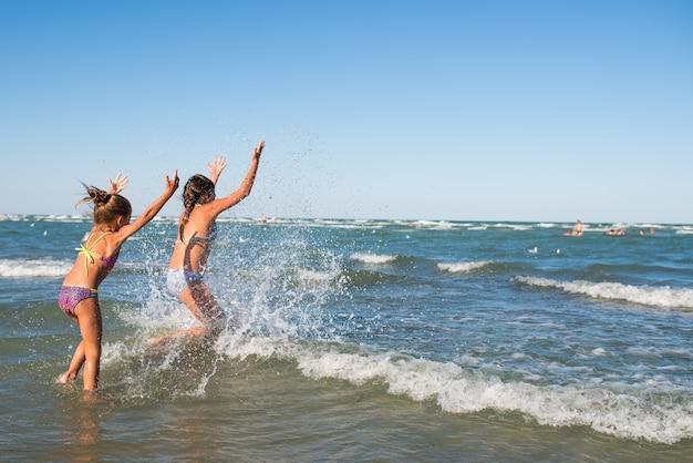 Positieve kleine meisjes rennen langs de stormachtige golven op een zonnige warme zomerdag