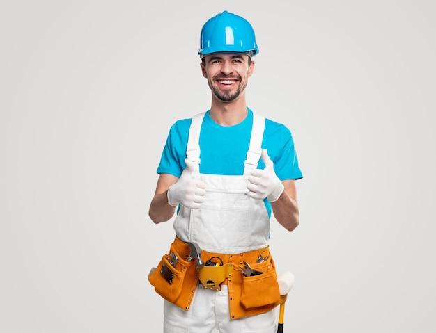 Positieve klusjesman in het algemeen en bouwvakker met toolkit die duimen toont en helder glimlacht