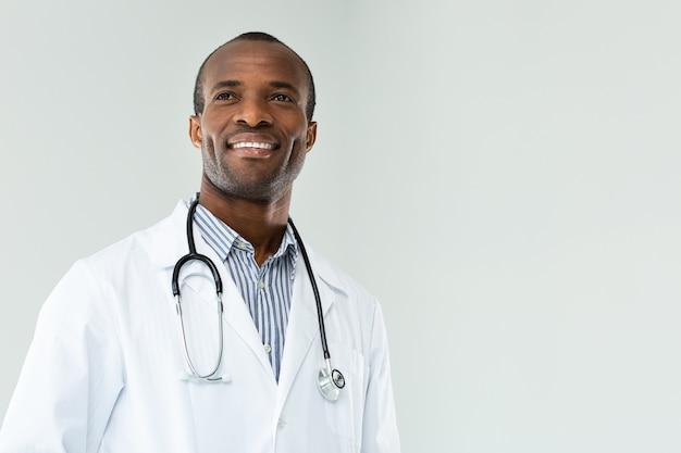Positieve knappe afro amerikaanse arts die lacht terwijl hij tegen een witte muur staat