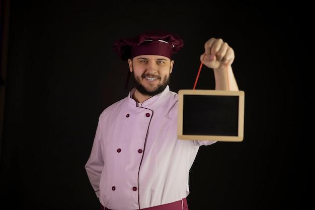 Positieve knappe bebaarde chef-kok in uniform houdt leeg schoolbord