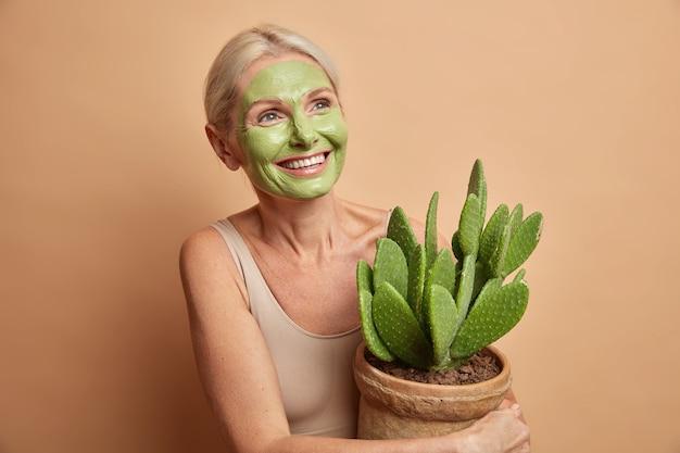 Positieve knappe europese vrouw senior vrouw past groene schoonheid masker houdt cactus in pot gekleed in vrijetijdskleding geïsoleerd over beige muur