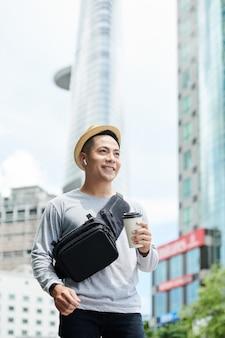 Positieve knappe jonge aziatische man in zonnehoed en draadloze koptelefoon met koffiekopje en wandelen in de grote stad