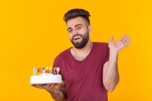 Positieve knappe jonge hipster man in bordeauxrood t-shirt met felicitatie cake met inscriptie gelukkige verjaardag poseren op een gele muur. concept van gelukwensen en jubilea.