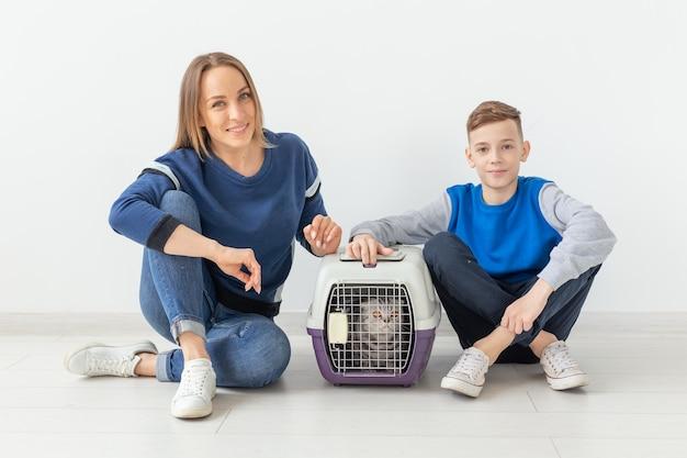 Positieve knappe moeder en zoon lanceren hun mooie grijze scottish fold-kat na de verhuizing in hun nieuwe appartement. housewarming concept.