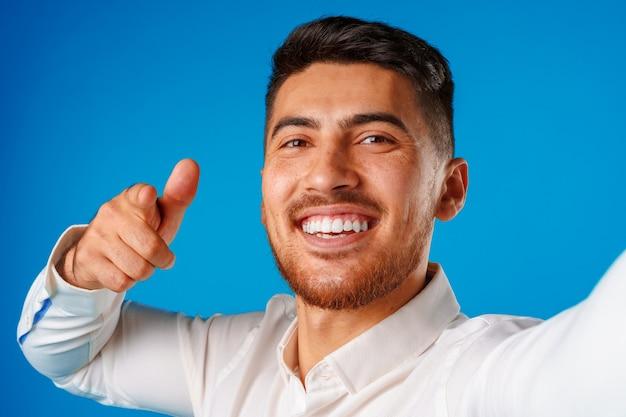 Positieve knappe spaanse zakenman die duim op gebaar toont