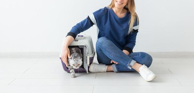 Positieve knappe vrouw en mooie grijze scottish fold-kat in haar nieuwe appartement na de