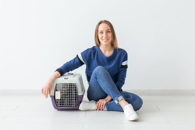 Positieve knappe vrouw en mooie grijze scottish fold-kat in haar nieuwe appartement