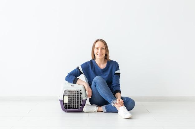 Positieve knappe vrouw en mooie grijze scottish fold-kat na de verhuizing haar nieuwe appartement binnen