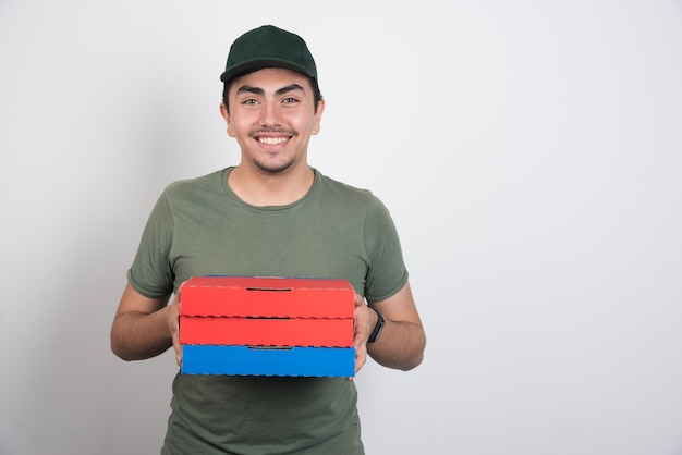 Positieve koerier die drie dozen pizza op witte achtergrond houdt.