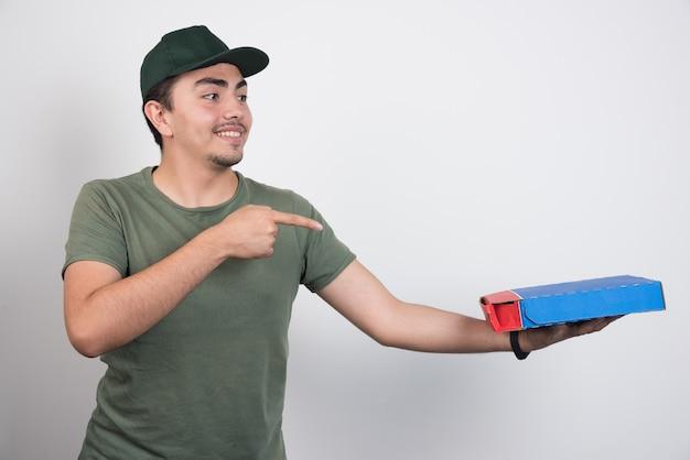 Positieve koerier wijzend op pizza en duimen opdagen op witte achtergrond.