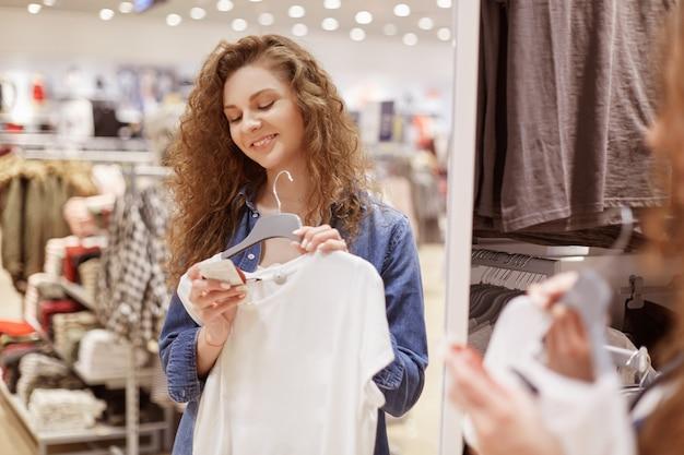 Positieve krullende jonge vrouw met opgetogen uitdrukking, maakt winkelen, houdt witte nieuwe blouse op hangers, leest informatie op etiket
