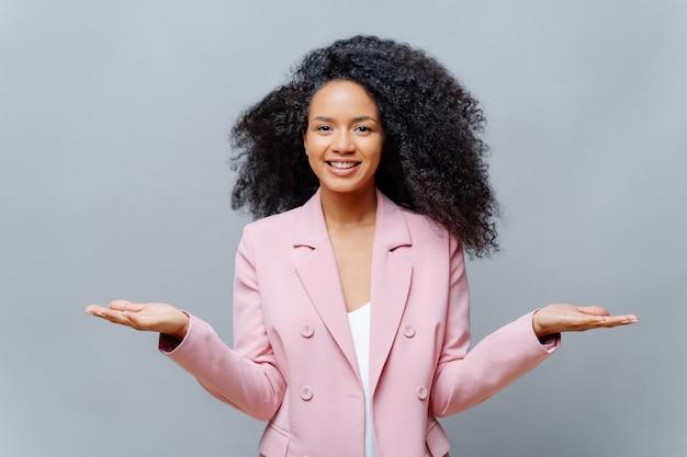 Positieve krullende vrouw met lichtgevend haar en vrijetijdskleding