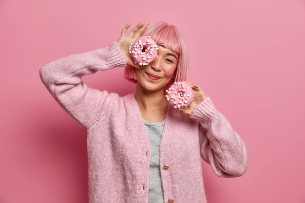Positieve lachende aziatische vrouw heeft plezier en houdt twee heerlijke donuts, speelt met suikerhoudende producten, geniet van smakelijk dessert, draagt casual trui,