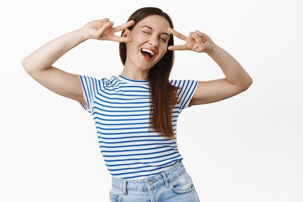 Positieve lachende brunette vrouw toont vrede v-teken, lachen, knipogen en zorgeloos kijken, positiviteit en vreugde, gelukkige mensen concept, witte muur.