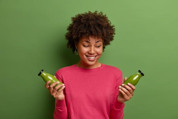 Positieve lachende gekrulde haired vrouw vormt met twee glazen flessen groene detox smoothie, drinkt gezonde verse vegetarische drank met vitamims, draagt roze trui, houdt zich aan dieet, vormt binnen.