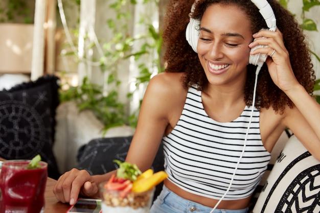 Positieve lachende gemengd ras jonge vrouw rust in café interieur chats met vrienden in sociale netwerken, favoriete liedjes in afspeellijst zoekt, mobiele applicatie gebruikt, zit op comfortabele bank.