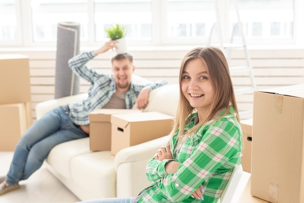 Positieve lachende jonge meisje zittend tegen haar lachen wazig echtgenoot in een nieuwe woonkamer terwijl