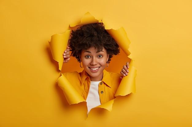 Positieve lachende meisje met krullend kapsel, gekleed in een modieuze gele jas, vormt door gescheurd papier achtergrond, witte tanden vertoont, geniet van een geweldige dag, in een goed humeur.