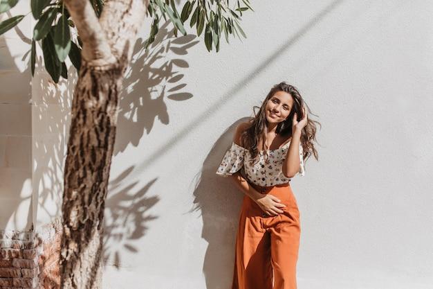 Positieve langharige dame in oranje zomerbroek met glimlach kijkt naar voren op witte muur met olijfboom