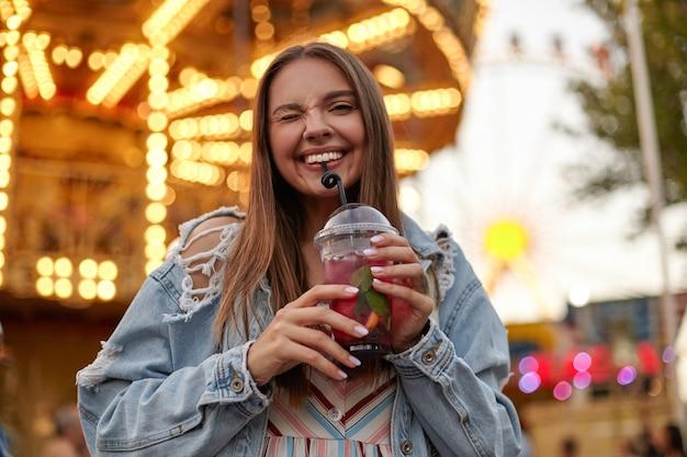 Positieve langharige jonge mooie vrouw in trendy jeans jas poseren over park van attracties, knipogen geven en breed glimlachen terwijl het drinken van limonade met stro
